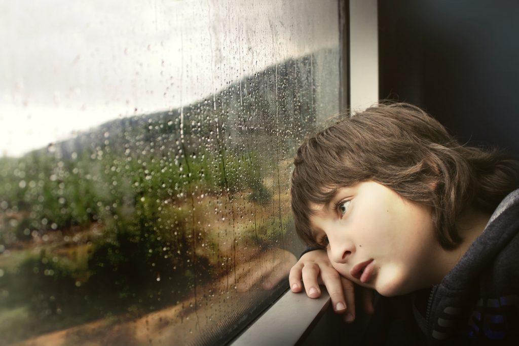 Kind am Fenster im Regen