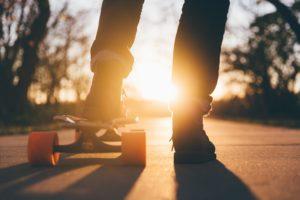 Kind auf Skateboard im Sonnenuntergang